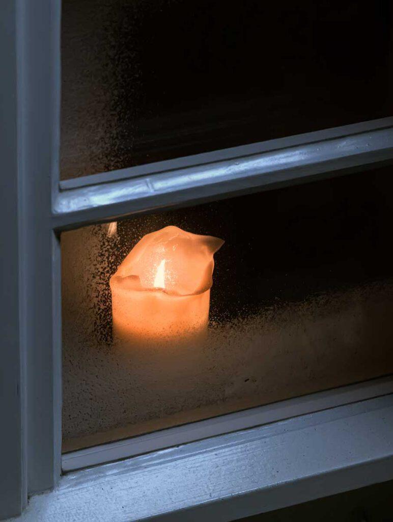 An Heiligabend eine Kerze ins Fenster